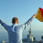 A US Navy crewman signals the letter 'U' using flag semaphore during an underway replenishment exercise (2005)